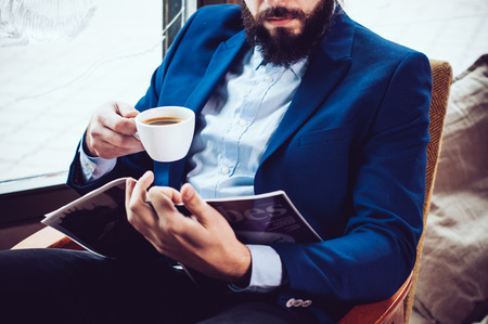 magazine reading: Young businessman in a blue jacket with a cup of coffee, reading a magazine in a cafe