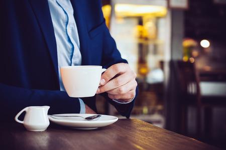 tomando café: Hombre de negocios en una chaqueta azul con una taza de café en el café en la tabla, primer plano Foto de archivo