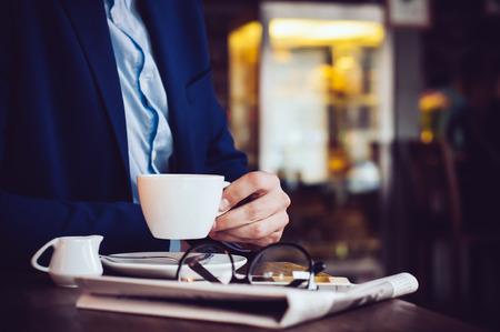 Hombre de negocios en una chaqueta azul con una taza de café, gafas de lectura, prensa y teléfono inteligente en un café en la mesa, close-up