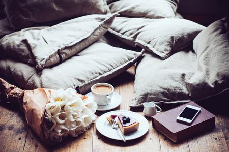 Kussens, een boeket van tulpen, koffie met melk, cheesecake en smartphone op een armoedige houten vloer. Hipster levensstijl