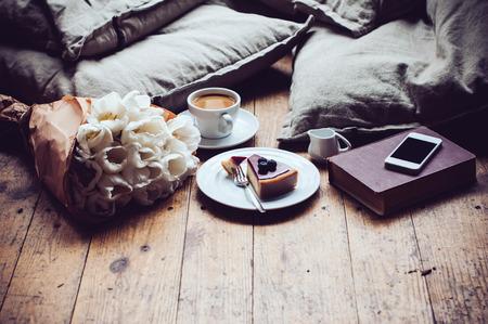 Almohadas, un ramo de tulipanes, café con leche, pastel de queso y el teléfono inteligente en un piso de madera en mal estado. Estilo de vida inconformista Foto de archivo - 37672302