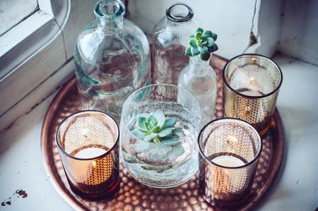 Old bottles, candles on a copper vintage tray, vintage home decor