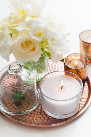 Bouquet of white flowers in a vase, candles on a copper tray vintage, wedding home decor Stock Photo