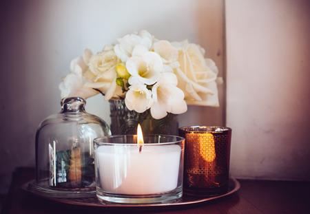 Ramo de flores blancas en un florero, velas en la bandeja de cobre de la vendimia, decoración del hogar de la boda en una mesa