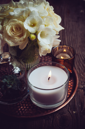 Bouquet of white flowers in a vase, candles on a copper vintage tray, wedding home decor on an old wooden board