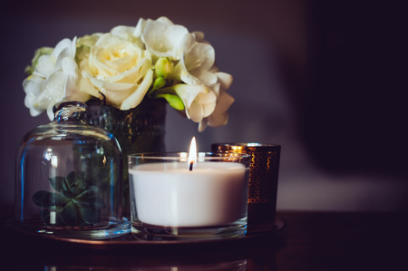 white candle: Bouquet of flowers in a vase, candles on a tray, vintage home decor on an a table, dark tones Stock Photo