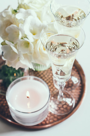 Glasses of champagne and candles: Bouquet of white flowers in a vase, candles and champagne on a copper tray vintage, wedding home decor