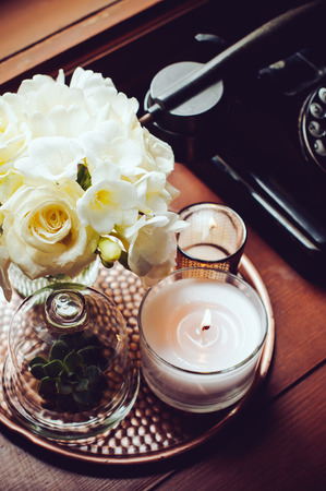 rotary phone: Bouquet of white flowers in a vase, candles on a copper vintage tray, old rotary phone, retro home decor Stock Photo