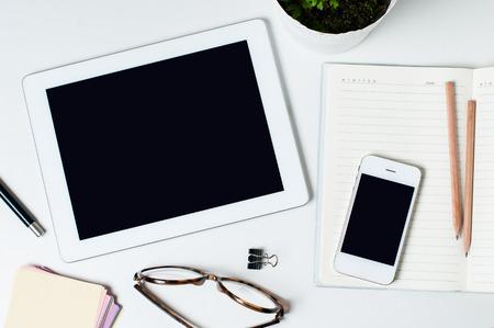 Desktop, biuro w domu: tabletki, notebooki, okulary, inteligentne, kwiat, długopisy i ołówki na białym tle