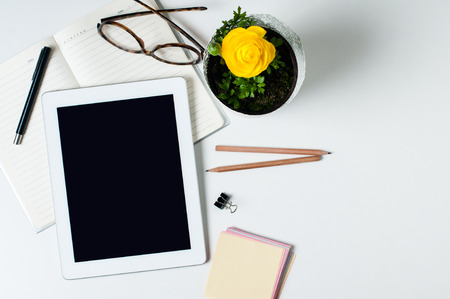 Desktop, home office: a tablet, notebooks, glasses, smart, flower, pens and pencils on a white background