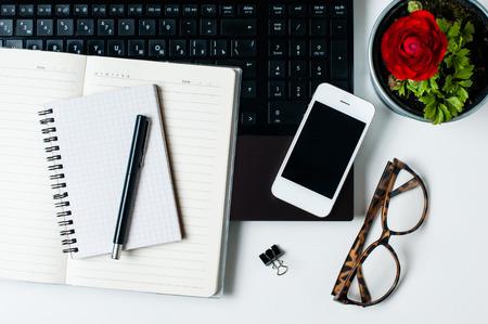 Tavolo ufficio, home office: un laptop, notebook, occhiali da lettura, smart phone, penna su uno sfondo bianco