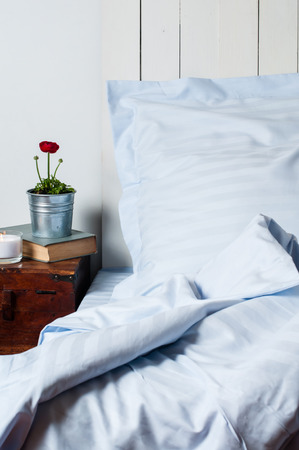 Bedroom in rustic style, pillow and blanket, blue linen, bedside table with a flower, close-up.