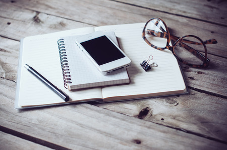 a lifestyle: Hipster home office tabletop: papers and notebooks, reading glasses, smart phone, pen on an old wooden board background Stock Photo