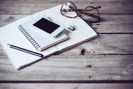 流行に敏感なホーム オフィス卓上: ペーパーおよびノート、老眼鏡、スマート フォン、古い木の板背景ペンします。ビンテージ ライフ スタイル。