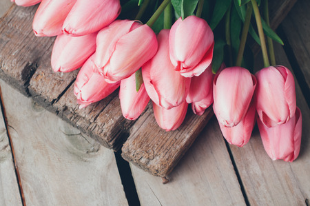 floral arrangements: Bunch of fresh spring pink tulips on old vintage wooden board, copy space