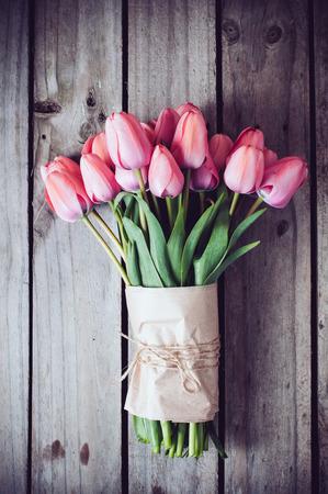 コピー領域の古いビンテージ木製ボード上の新鮮な春のピンクのチューリップの束