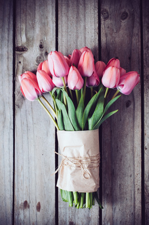 flower arrangement: Bunch of fresh spring pink tulips on old vintage wooden board, copy space