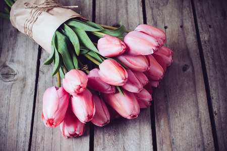 wedding table decor: Bunch of fresh spring pink tulips on old vintage wooden board, copy space