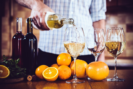 pours: Man pours white wine from a bottle into a glass, home kitchen interior, wine party. Stock Photo