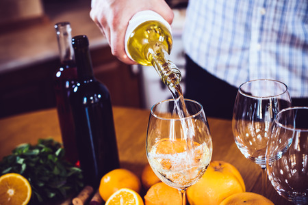 chilled: Man pours white wine from a bottle into a glass, home kitchen interior, wine party. Stock Photo