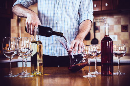 carafe: Man pouring red wine from bottle into a decanter, home kitchen interior, bottles of wine