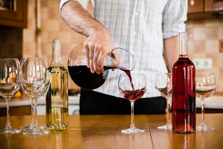Un homme verse du vin rouge de la carafe dans un verre, de l'intérieur de la cuisine de la maison
