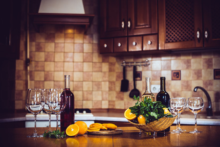 Wine bottles, crockery, glasses, fruit on the table, cozy home kitchen interior