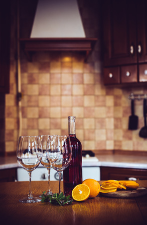 chilled: Wine bottles, crockery, glasses, fruit on the table, cozy home kitchen interior