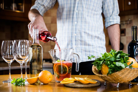 carafe: Man pouring red wine into a carafe, making sangria for home party, home kitchen interior. Homemade food and drinks