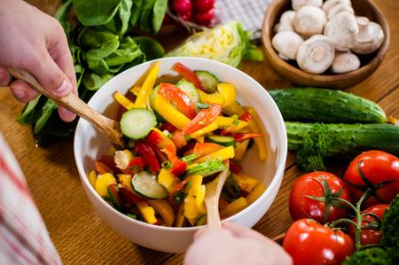 ensalada: Preparaci�n de la ensalada fresca de verduras, mezclar, verduras de primavera en la mesa de la cocina.