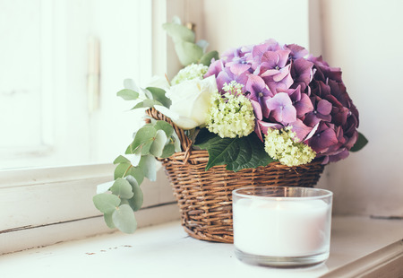 fresh: Big bouquet of fresh flowers, purple hydrangeas and white roses in a wicker basket on a windowsill, home decor, vintage style