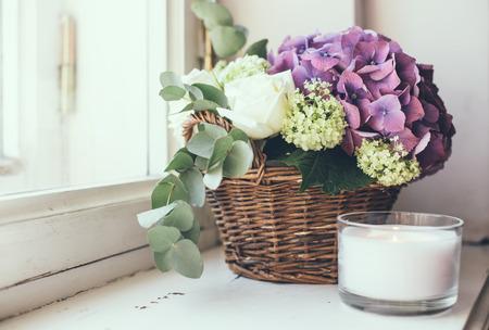 창턱, 가정 장식, 빈티지 스타일에 고리 버들 바구니에 신선한 꽃, 보라색 수국과 흰색 장미의 큰 꽃다발 스톡 콘텐츠