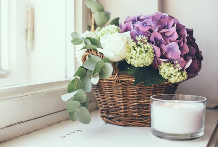 arreglo de flores: Gran ramo de flores frescas, hortensias moradas y rosas blancas en una cesta de mimbre en un alféizar, decoración del hogar, estilo vintage Foto de archivo