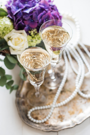 champagne party: Big bouquet of fresh flowers, purple hydrangeas and white roses in a wicker basket, two glasses of champagne and vintage wedding decor with pearls on a table