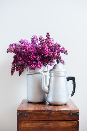 Home interior decor, bouquet of lilacs in a vase and vintage coffee pot on a wooden table on a white wall background photo