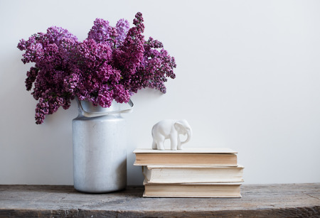 Huis interieur, boeket van seringen in een vaas en boeken op rustieke houten tafel, op een witte muur achtergrond