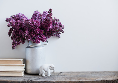 purple: Home interior decor, bouquet of lilacs in a vase and books on rustic wooden table, on a white wall background Stock Photo