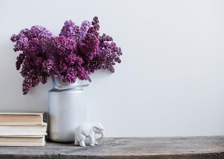 decoracion mesas: Interior del hogar decoración, ramo de lilas en un florero y libros sobre la mesa de madera rústica, en una pared blanca de fondo Foto de archivo