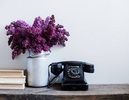 single shelf: Home interior decor, bouquet of lilacs in a vase, a vintage rotary phone and books on rustic wooden table, on a white wall background