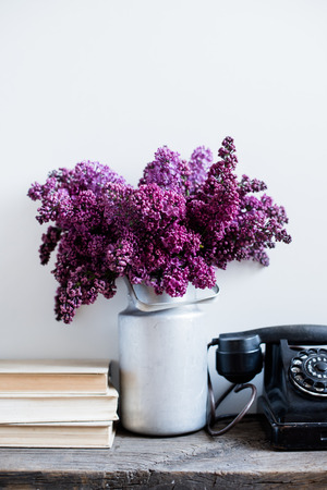 Home interior decor, bouquet of lilacs in a vase, a vintage rotary phone and books on rustic wooden table, on a white wall background photo