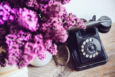 ホーム インテリア、花瓶、ビンテージ ロータリー電話、素朴な木製のテーブル, 白い壁の背景上の本のライラックの花束