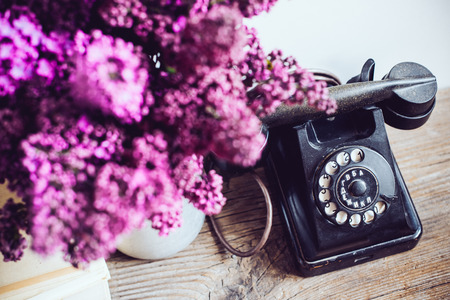 Home interior decor, bouquet of lilacs in a vase, a vintage rotary phone and books on rustic wooden table, on a white wall background