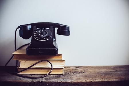 흰색 벽 배경에 검은 색 빈티지 로타리 전화와 소박한 나무 테이블에 책,