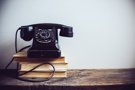 Black vintage rotary phone and books on rustic wooden table, on a white wall background Stockfoto