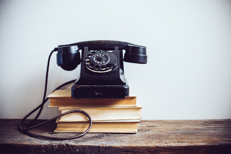 Black vintage rotary phone and books on rustic wooden table, on a white wall background Imagens