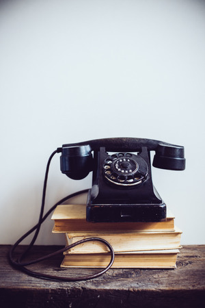 single shelf: Black vintage rotary phone and books on rustic wooden table, on a white wall background Stock Photo