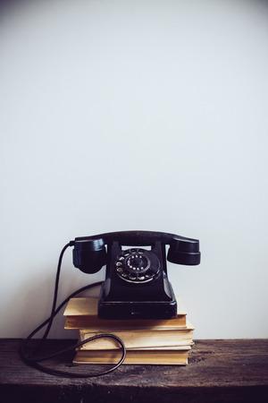 Zwarte vintage roterende telefoon en boeken op rustieke houten tafel, op een witte muurachtergrond Stockfoto