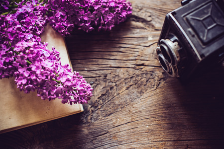 Books, notebooks, vintage camera and lilac flowers on an old wooden board background, hipster lifestyle composition photo