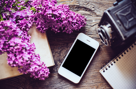 Books, notebooks, vintage camera, white smart phone and lilac flowers on an old wooden board background, hipster lifestyle arrangement Stock Photo