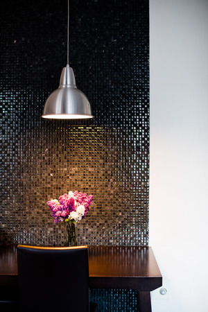 lamp house: Bunch of lilac on the table in the local lighting by the wall, a modern kitchen interior closeup
